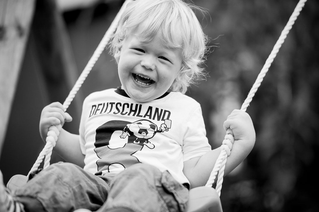 happy boy laughing on swing