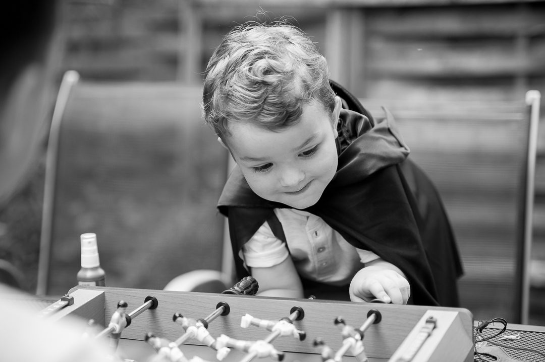 boy in batman costume playing table soccer