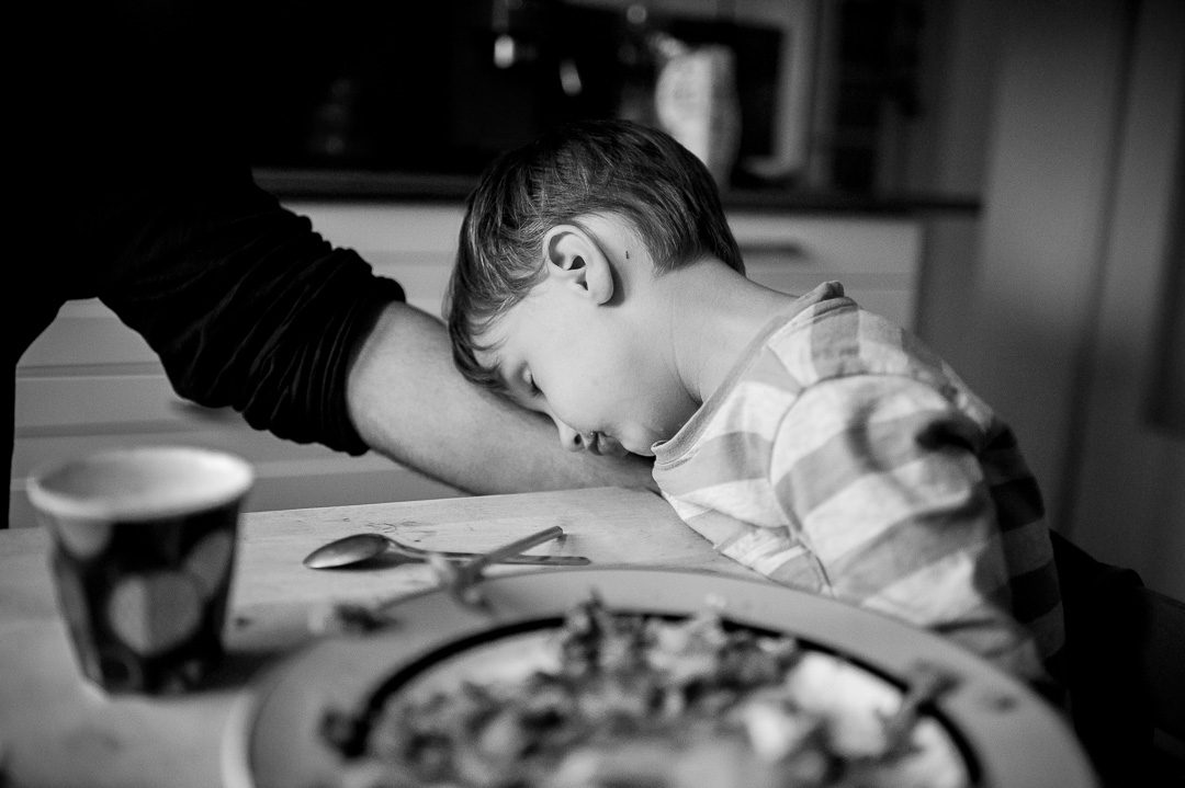 boy falling asleep at dinner table