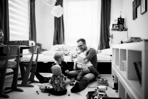 father and three children playing in nursery