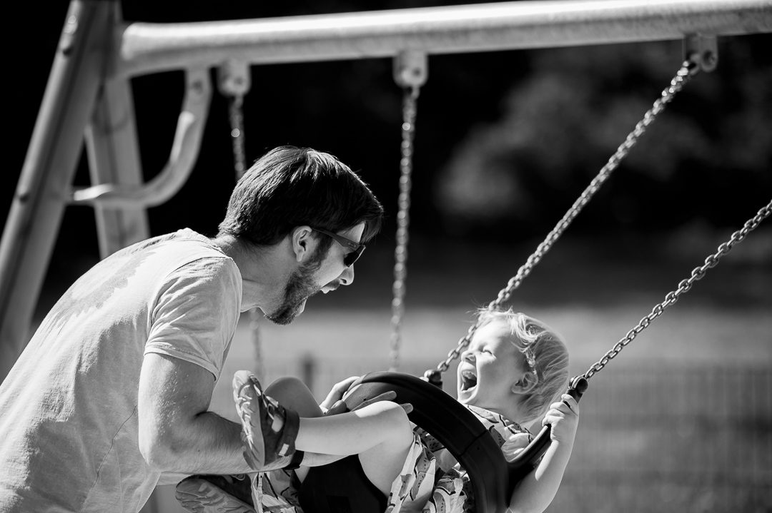 daughter on a swing laughing with father