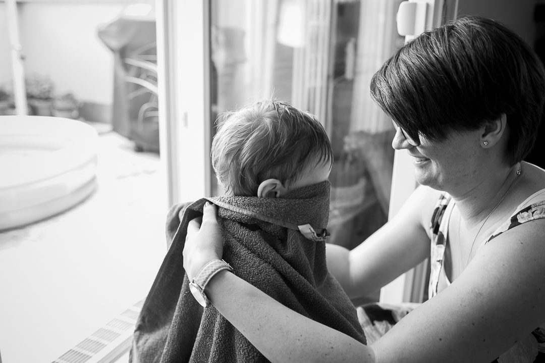 mother wrapping son in towel after a bath