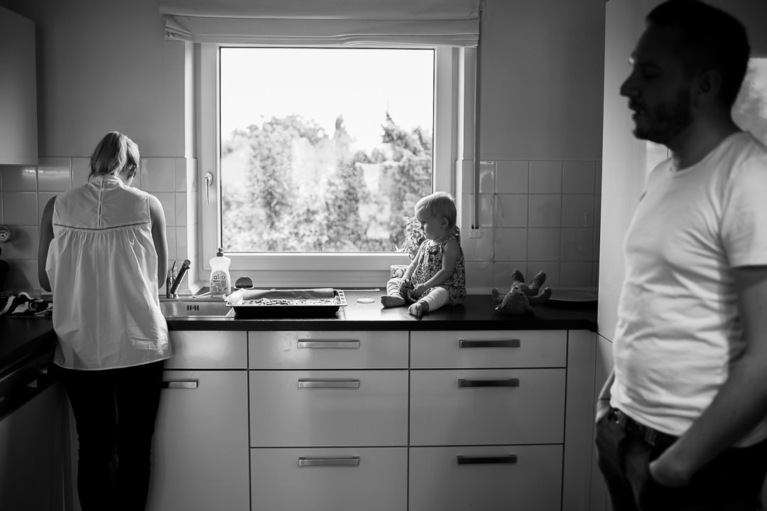 little girl on kitchen counter watching mother preparing dinner