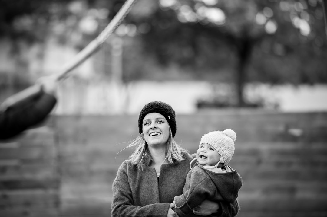 mother and daughter watch son on swing during documentary family photo shoot by Petsy Fink