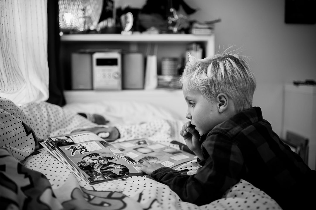toddler reading a book about superheroes