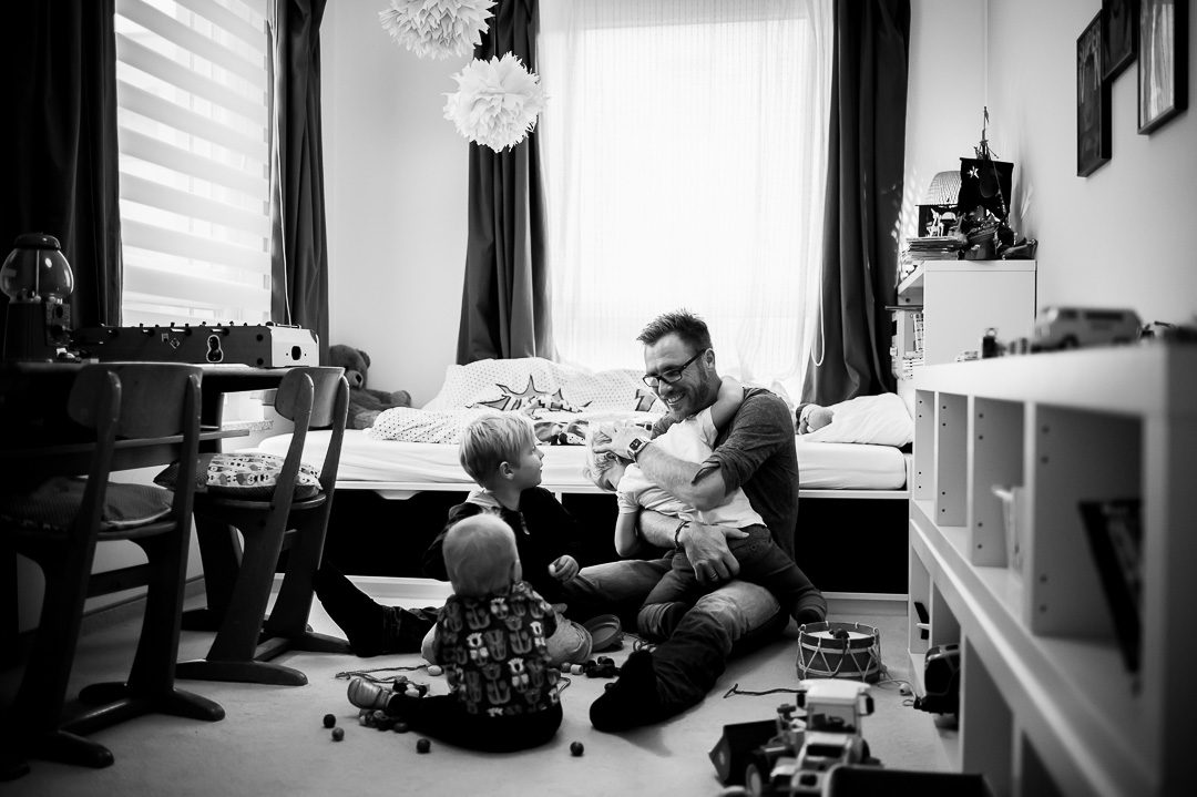 father sitting on floor and playing with three children in kids room