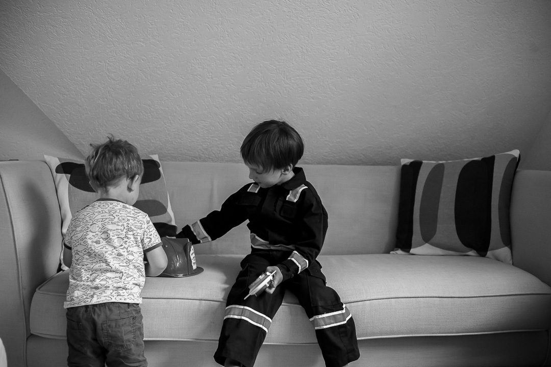 boy in firebrigade uniform playing with brother