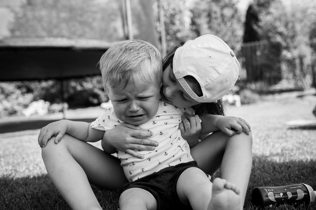 big sister is cuddling little brother in black and white photograph