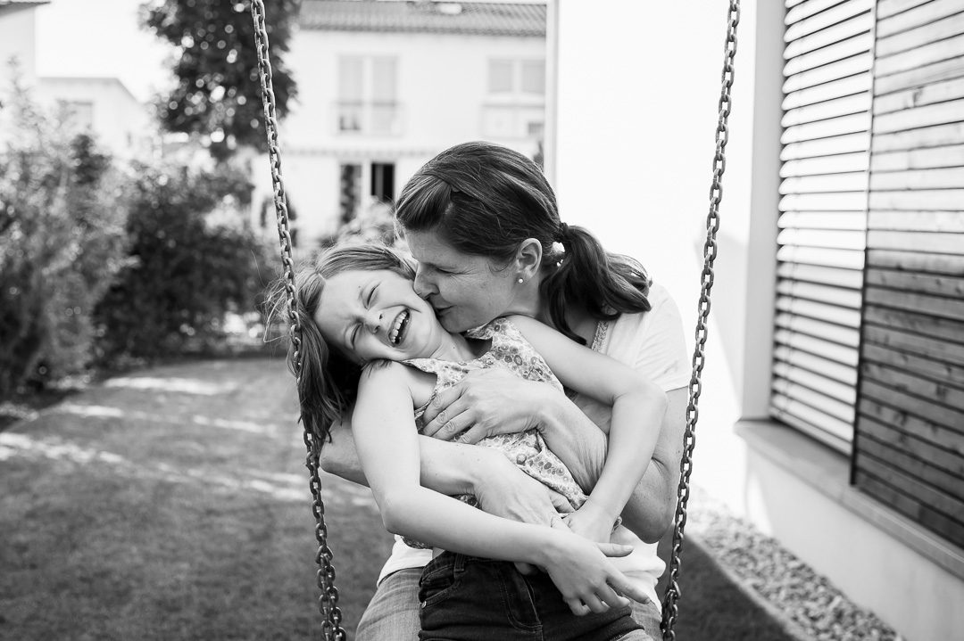 mother and daughter cuddle on swing