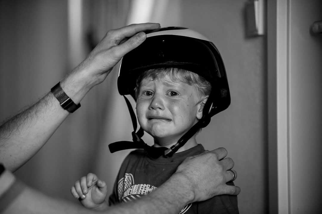 little boy with bike helmet crying