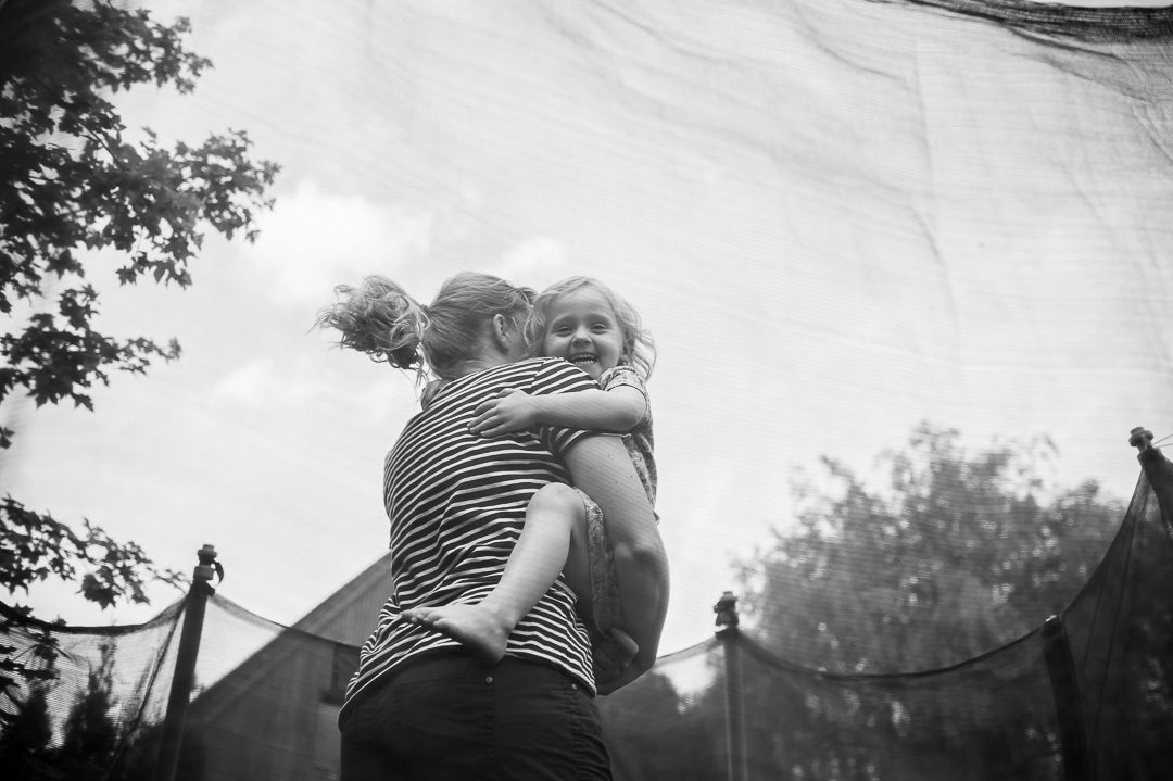 mother and daughter on trampoline during documentary family photo shoot