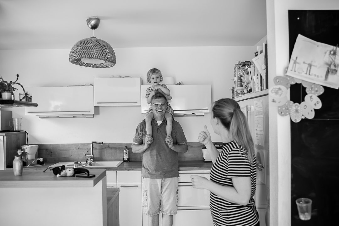 parents have a laugh with daughter in the kitchen